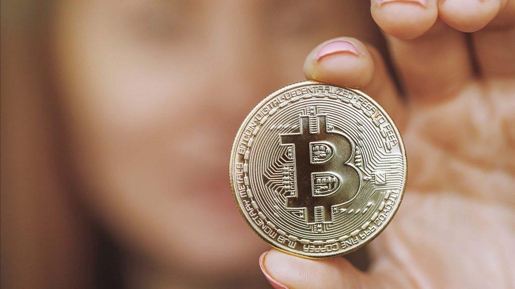 Anonyme Frau mit Bitcoin-Münze